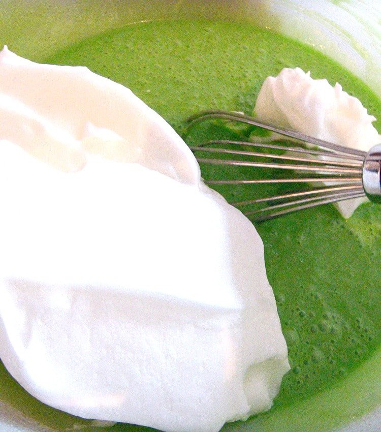 Pandan Chiffon Cake showing how to add the whisked egg whites to the batter