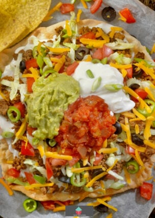 Taco Pizza, delicious homemade pizza dough with toppings of a taco! Tasty seasoned ground beef, onions, garlic, olives, tomato sauce, topped with cheese, sour cream and lettuce.